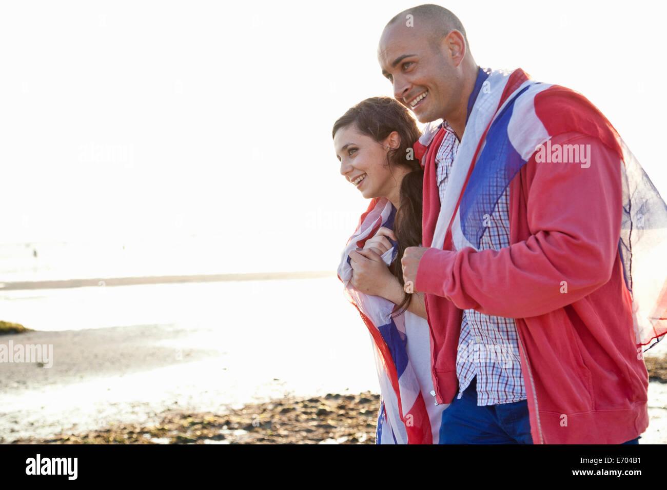 Paar verpackt in britische Flagge, ein Spaziergang am Strand von Bournemouth, Dorset, Großbritannien Stockbild