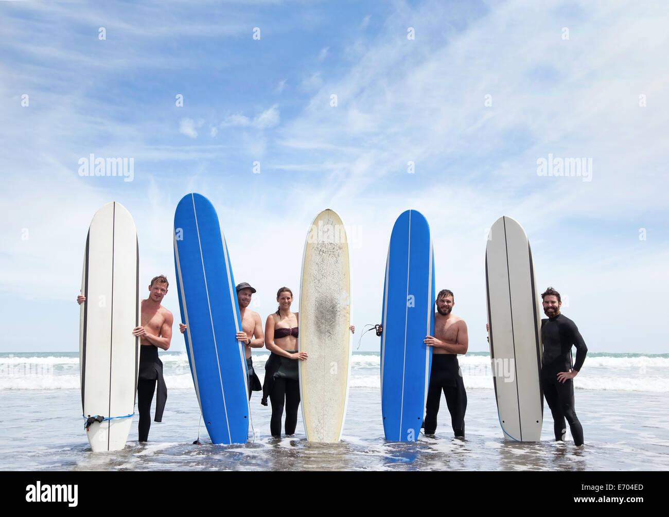 Gruppenbild der männlichen und weiblichen Surfer-Freunde im Meer mit Surfbrettern stehend Stockbild