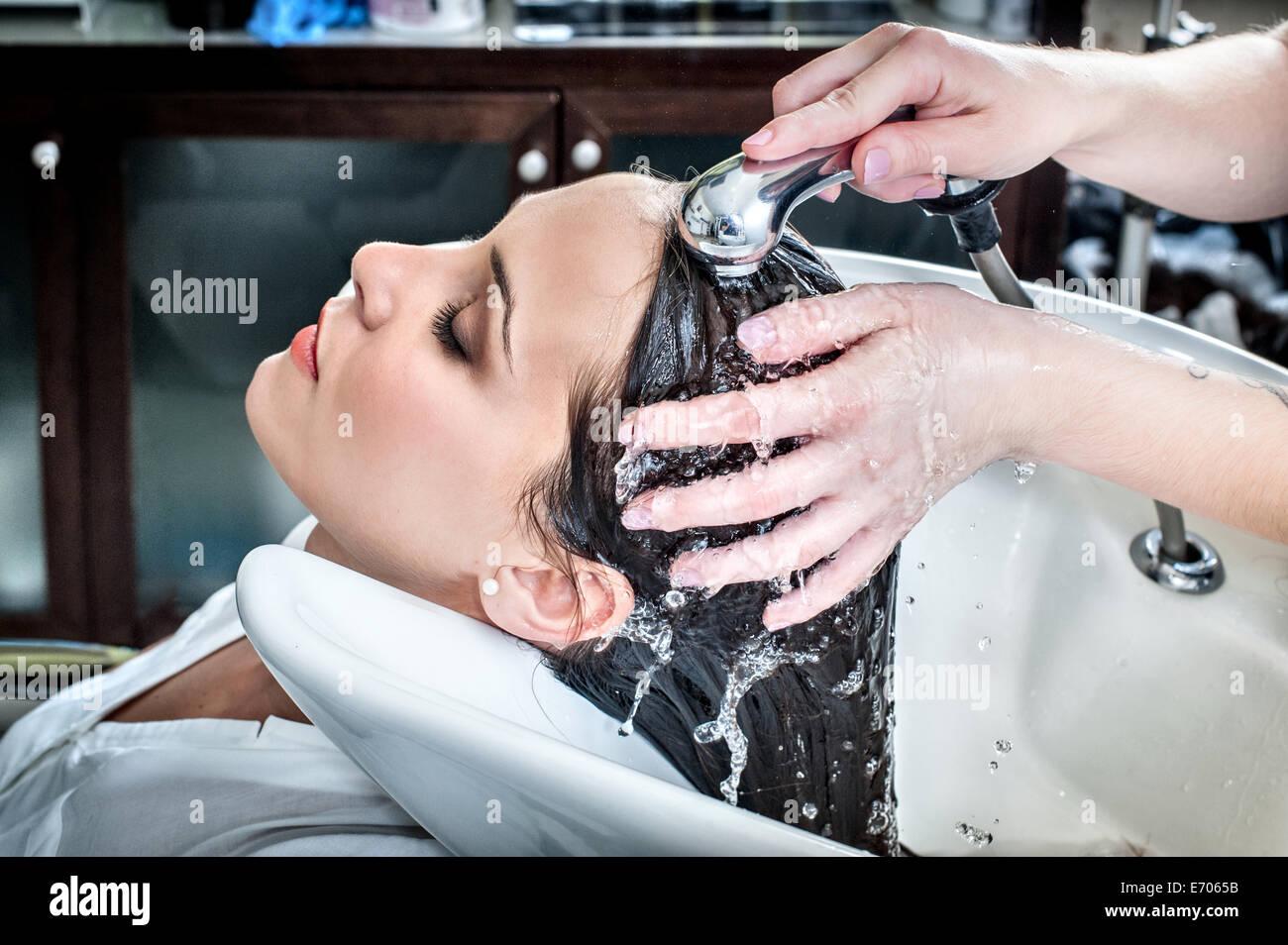 Weibliche Friseur spülen junge Frau an den Haaren in Friseursalon Stockbild