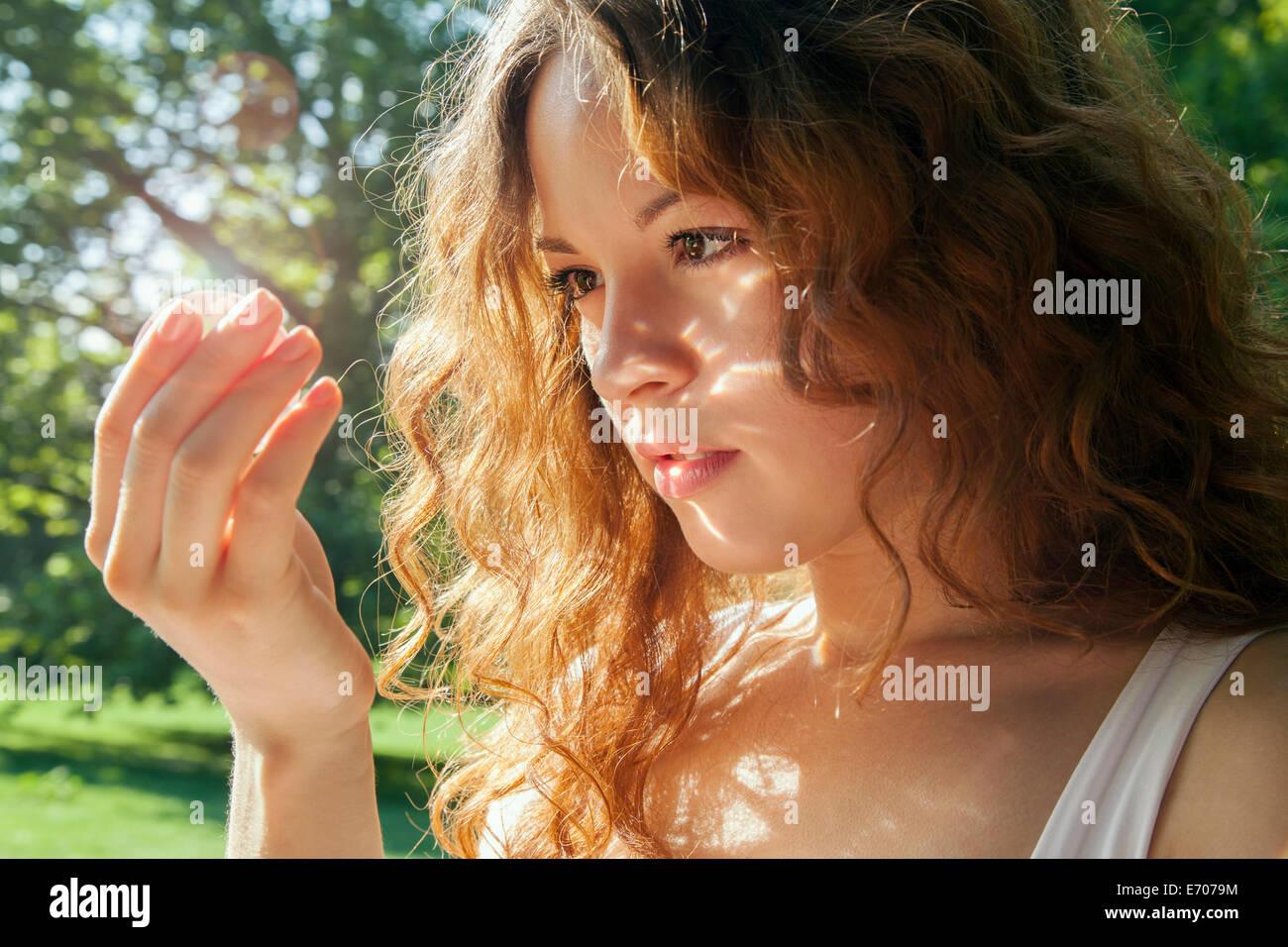 Porträt der jungen Frau blickte auf etwas in der hand glühend Stockbild