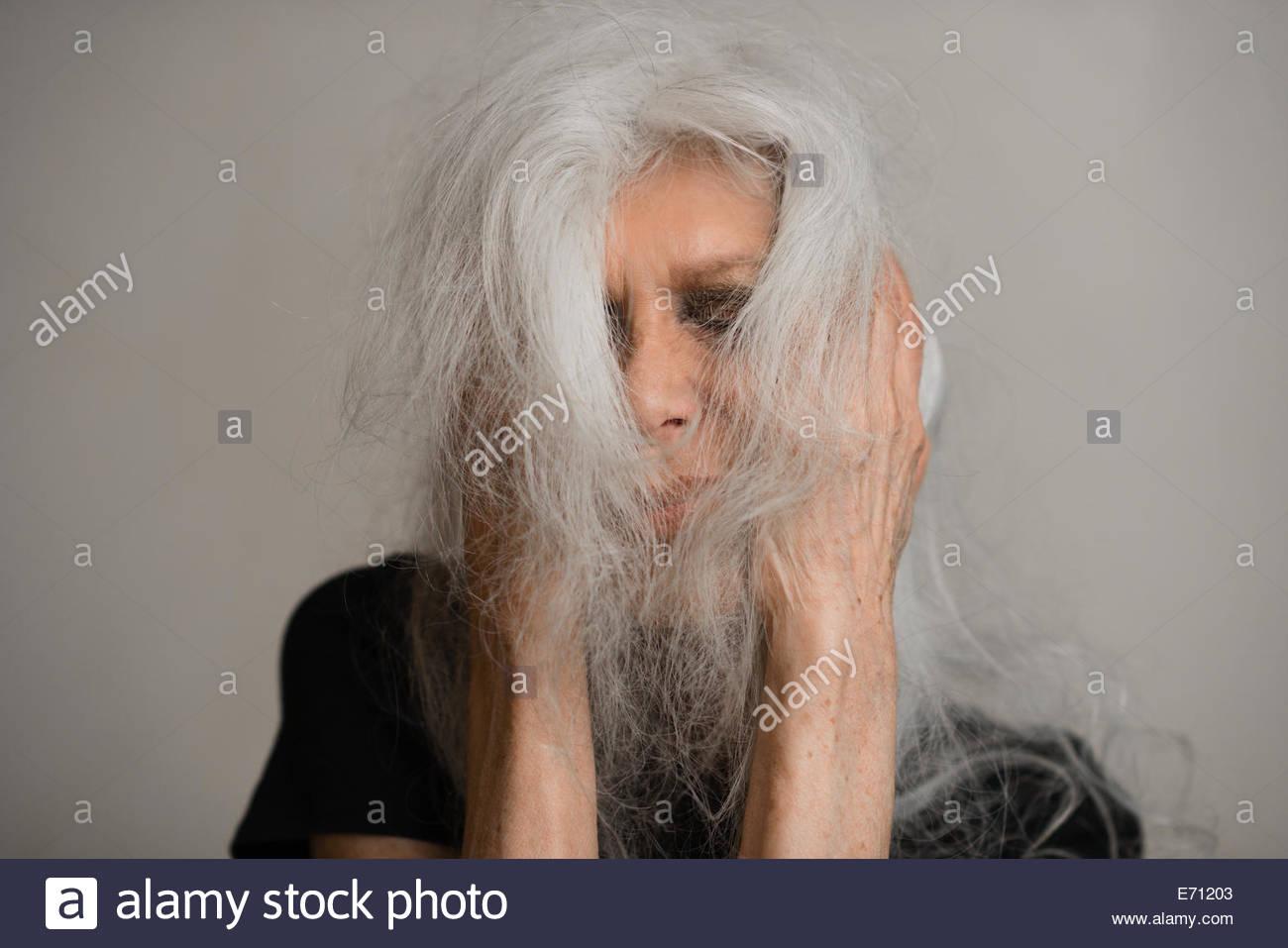 Studioportrait senior Frau mit langen grauen Haaren bedeckte Gesicht Nahaufnahme Stockbild