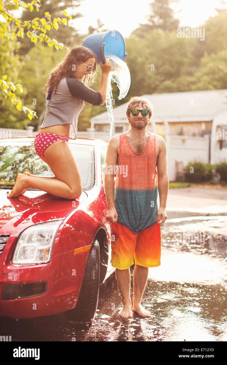 Junge Frau Gießen Eimer Wasser über den Kopf des Mannes Stockbild
