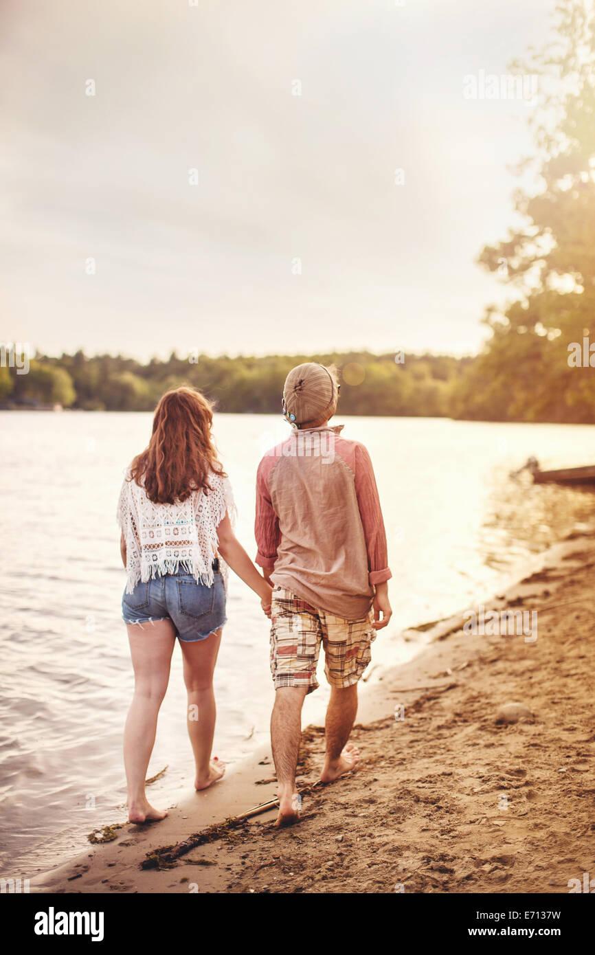 Junges Paar am Strand, die Hand in Hand gehen Stockbild