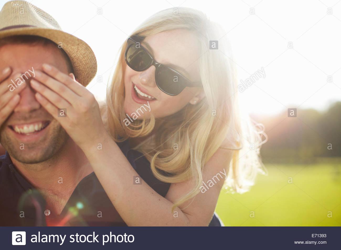 Junge Frau von Freund die Augen im park Stockbild
