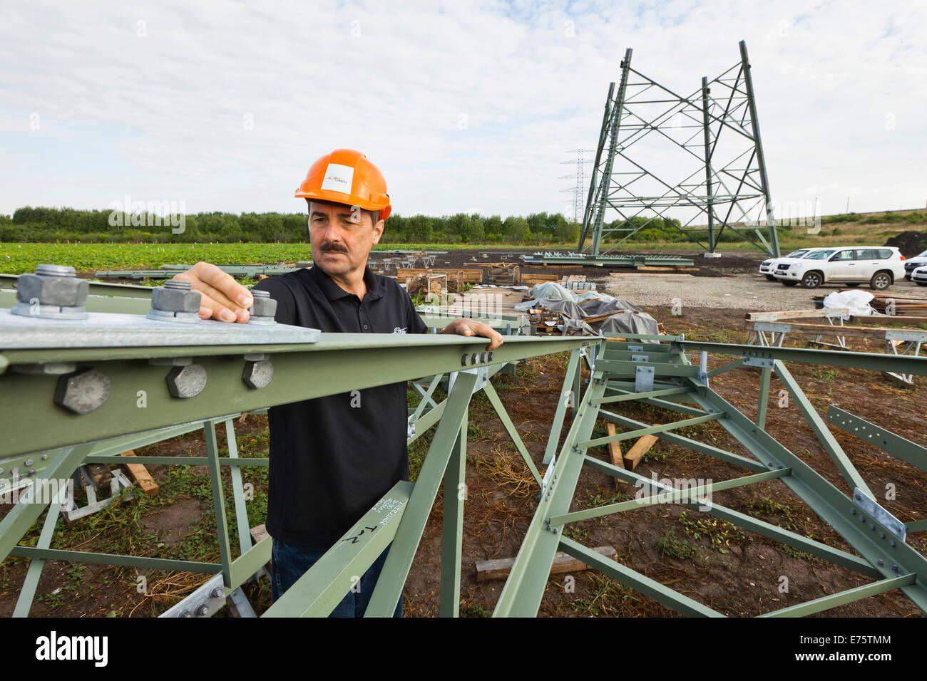 Ingenieur, Schraubverbindungen auf Segmente der extra Hochspannungsmasten von einer 380 kV Höchstspannung Hochspannungsleitung Stockbild