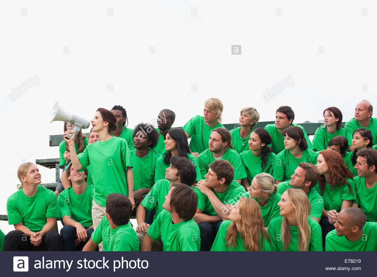 Gruppe von Zuschauern, eine Person mit Megaphon Stockbild