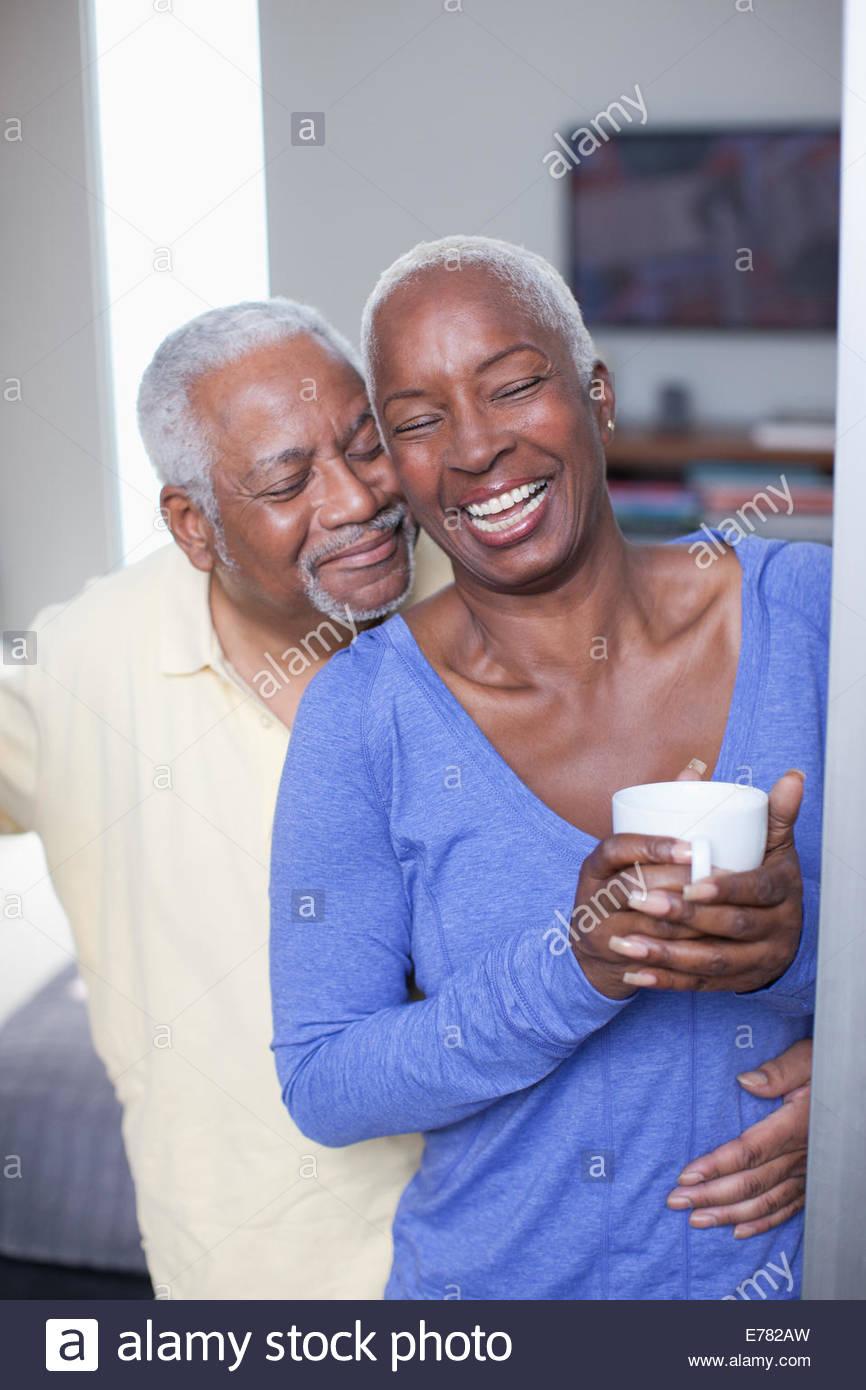 Älteres Ehepaar im Innenbereich umarmt lächelnd Stockbild