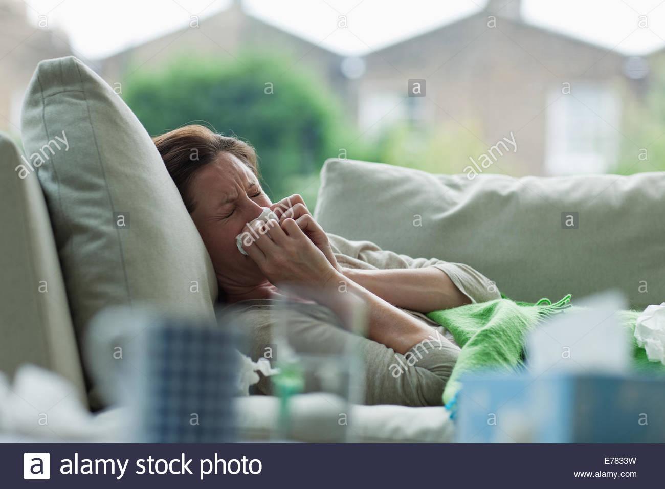 Kranke Frau Verlegung auf Sofa Nase weht Stockbild