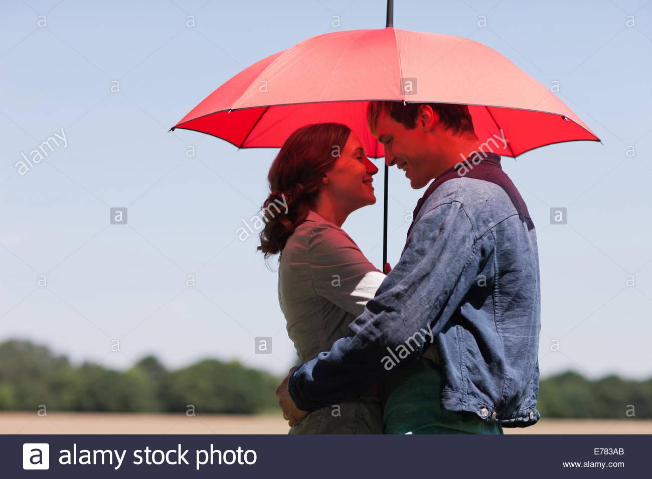 Paar umarmt unter roten Regenschirm Stockbild