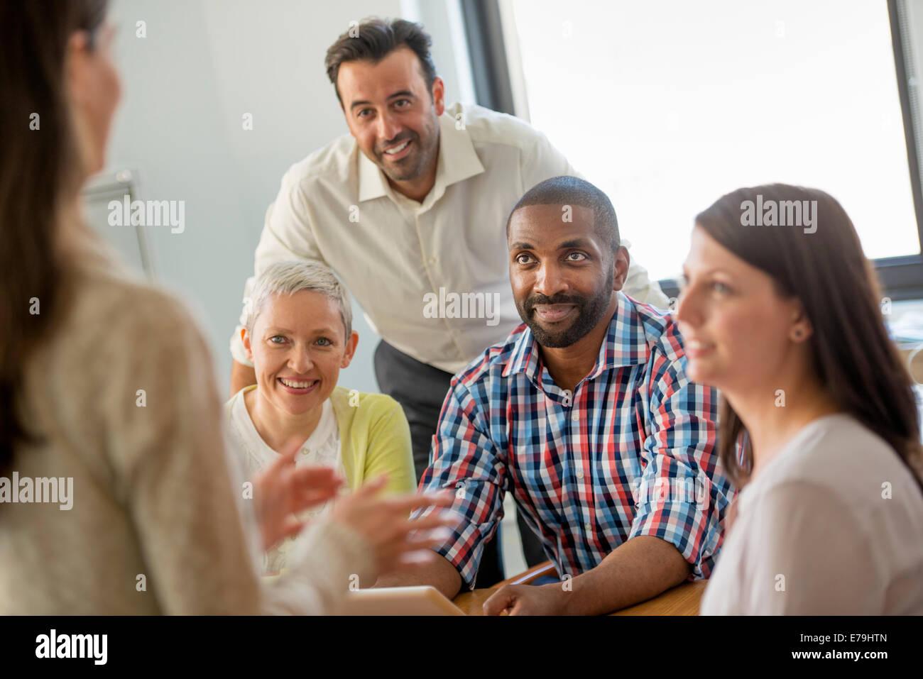 Fünf Menschen in einem Büro, zwei Männer und drei Frauen reden. Stockbild