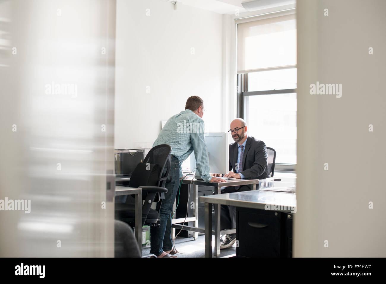 Büroalltag. Zwei Personen im Gespräch miteinander über einen Schreibtisch. Stockbild