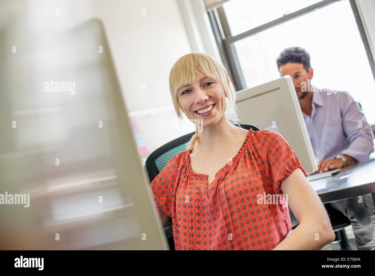 Büroalltag. Zwei Menschen sitzen am Schreibtisch mit dem Computer. Stockbild