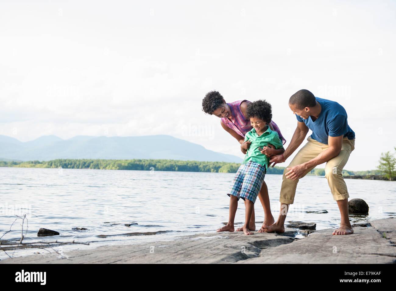 Familie, Mutter, Vater und Sohn spielen am Ufer eines Sees. Stockfoto