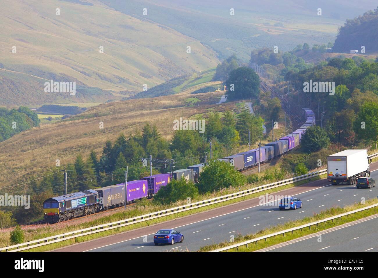 Direcr Rail Services (DRS) Diesel-Güterzug vorbei an der Autobahn M6 im Tal Flusses Lune. Howgills, Cumbria, Stockbild