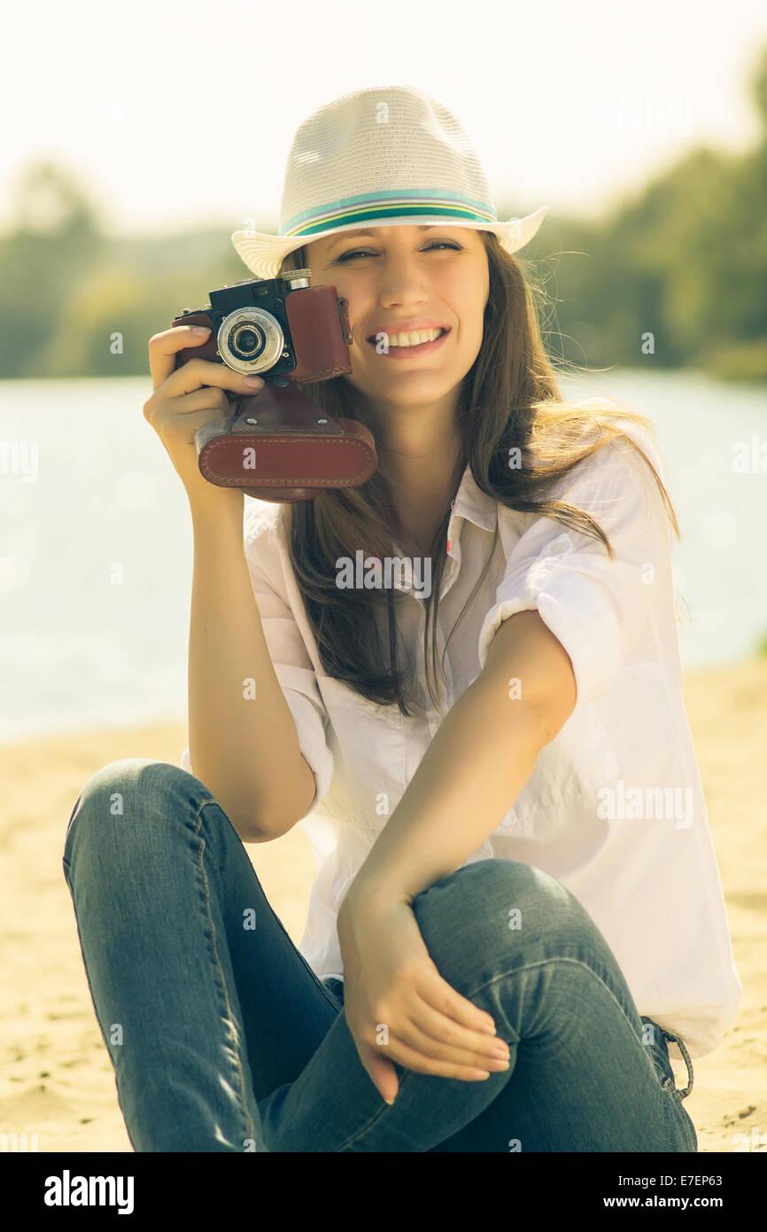 Junge Frau posiert mit alten Film-Kamera. Kaukasische Hipster Mädchen mit Hut lustige Zeit am Strand verbringen. Stockbild