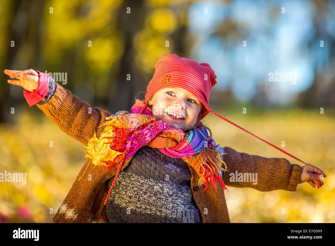 Glückliche kleine Mädchen spielen im Herbst park Stockbild