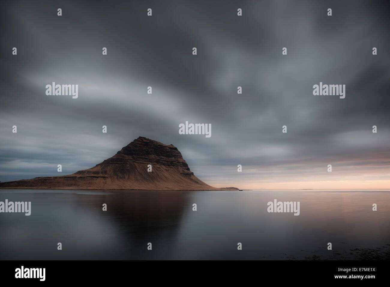 Der Berg Kirkjufell spiegelt sich im Wasser des Grundarfjordur Bucht bei Sonnenaufgang, Snaefellsnes Halbinsel, Stockbild