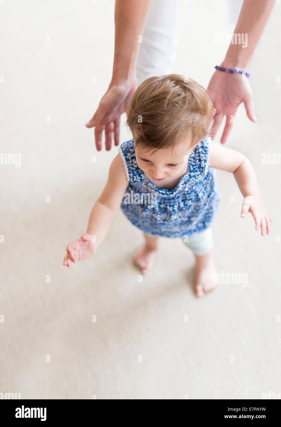 Mutter Mitarbeitende Tochter (18-23 Monate) bei ihren ersten Schritten Stockbild
