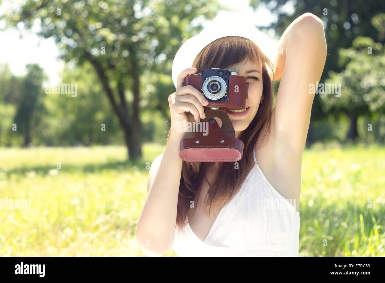 Junge hübsche Frau posiert mit alten Filmkamera im Sommerpark. Mädchen in weißen Hut Foto mit manuelle Stockbild