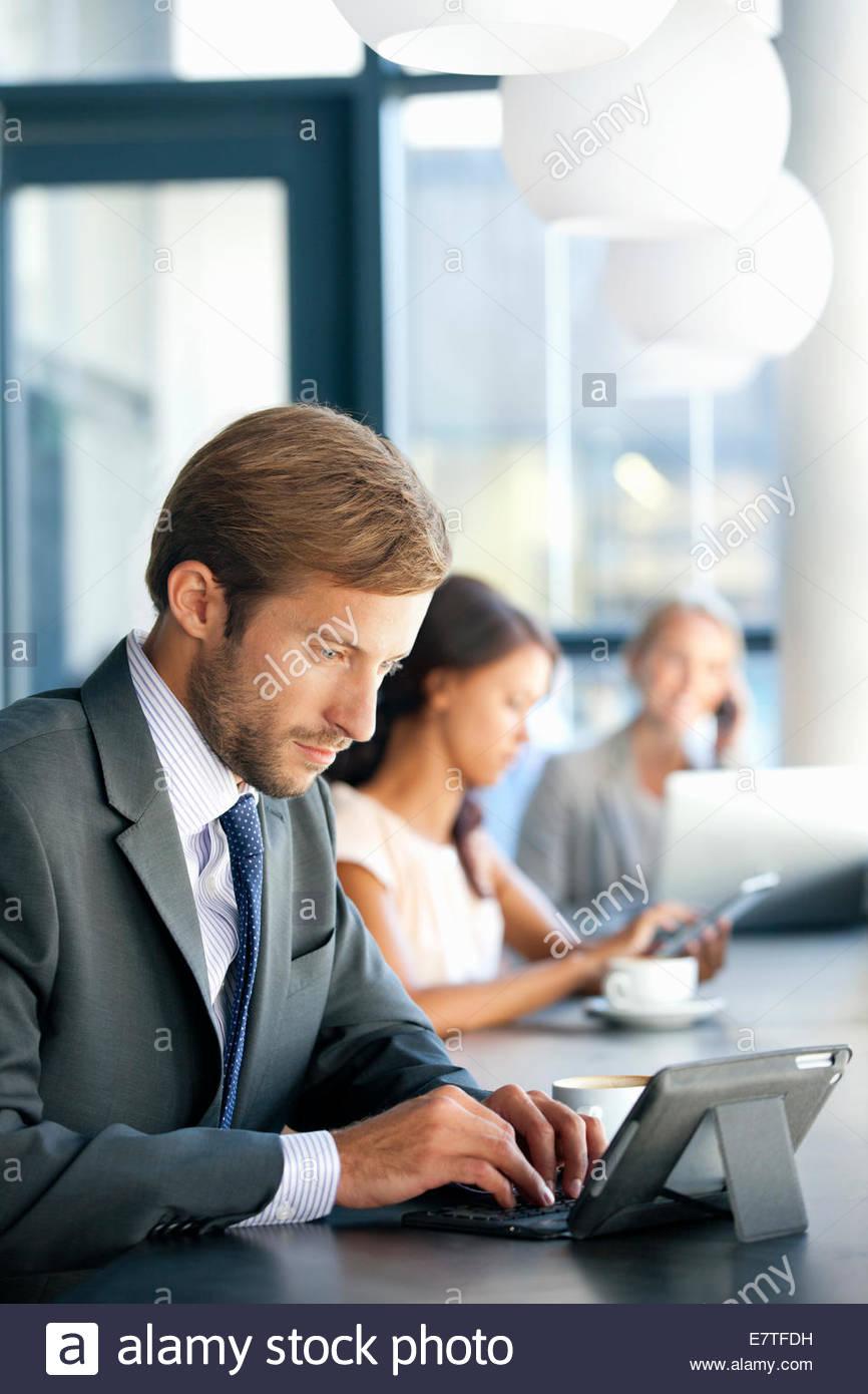 Neugierig Geschäftsmann mit digital-Tablette in Coffee-shop Stockbild