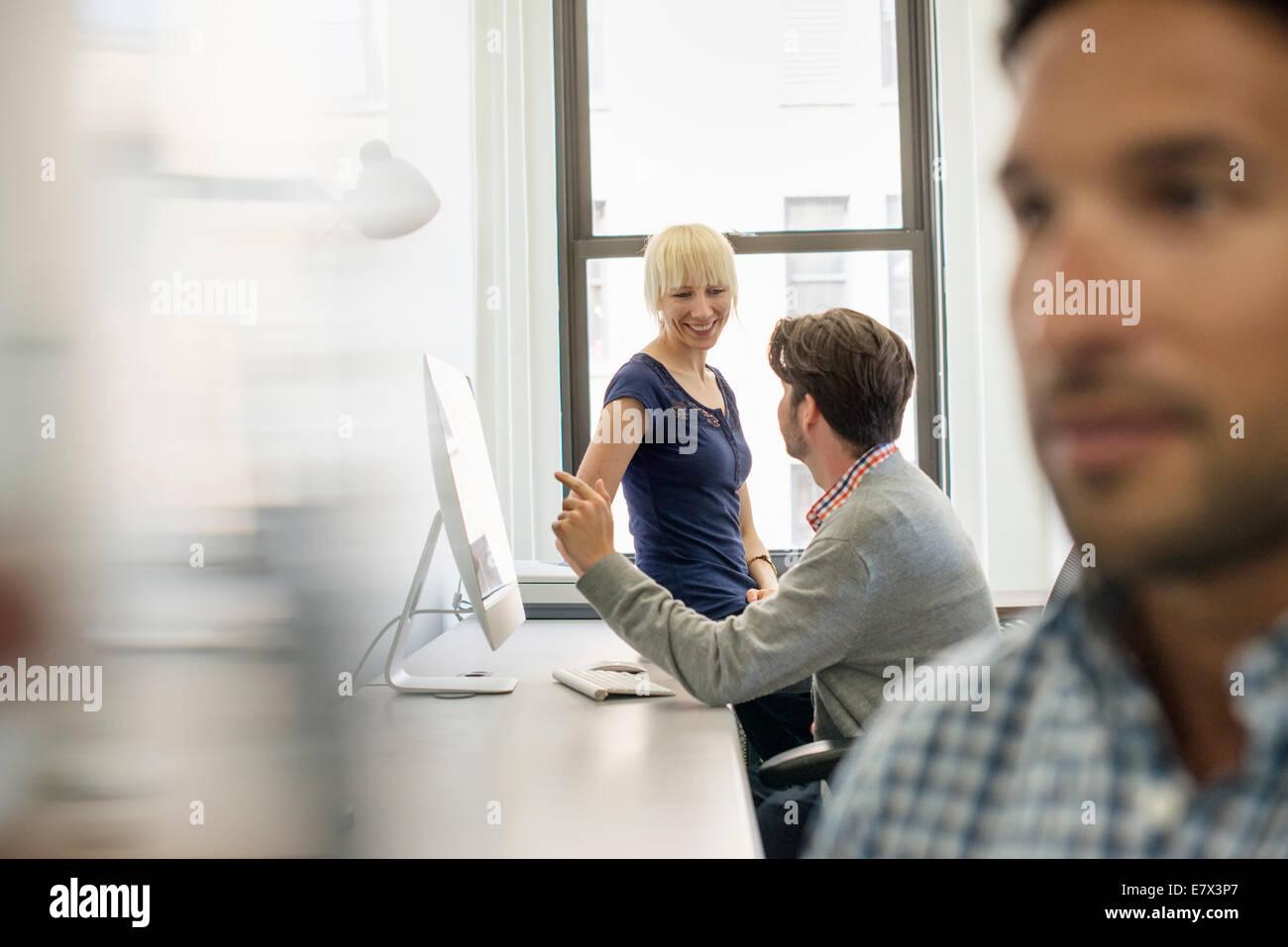 Drei Kollegen in ein Büro, zwei reden und einen Stand die Tür hören. Stockbild