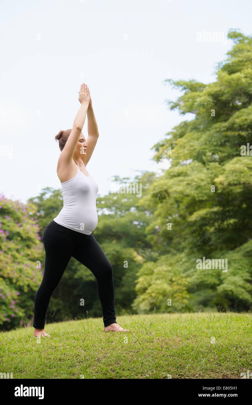 Schwangere Frau beim Yoga im park Stockbild