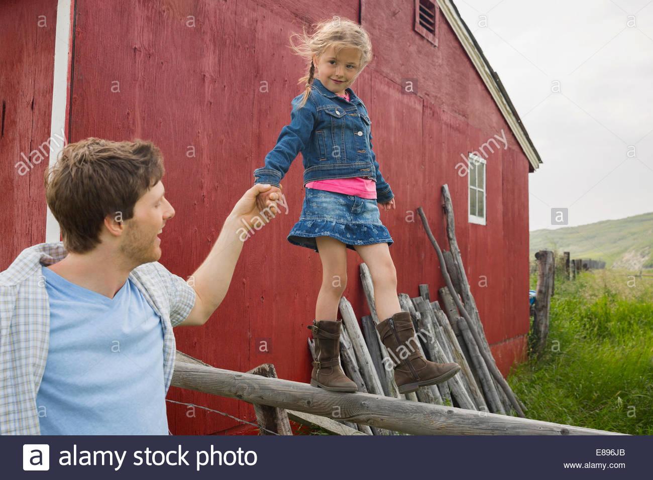 Vater Tochter Gleichgewicht auf ländlichen Zaun zu helfen Stockbild