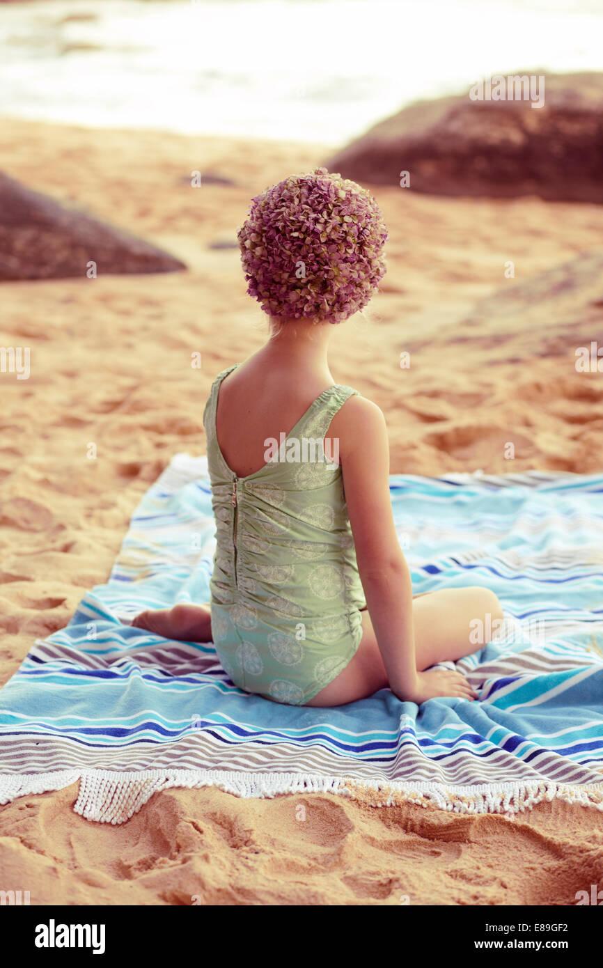 Mädchen in Swimcap sitzen auf Strand Decke Stockbild