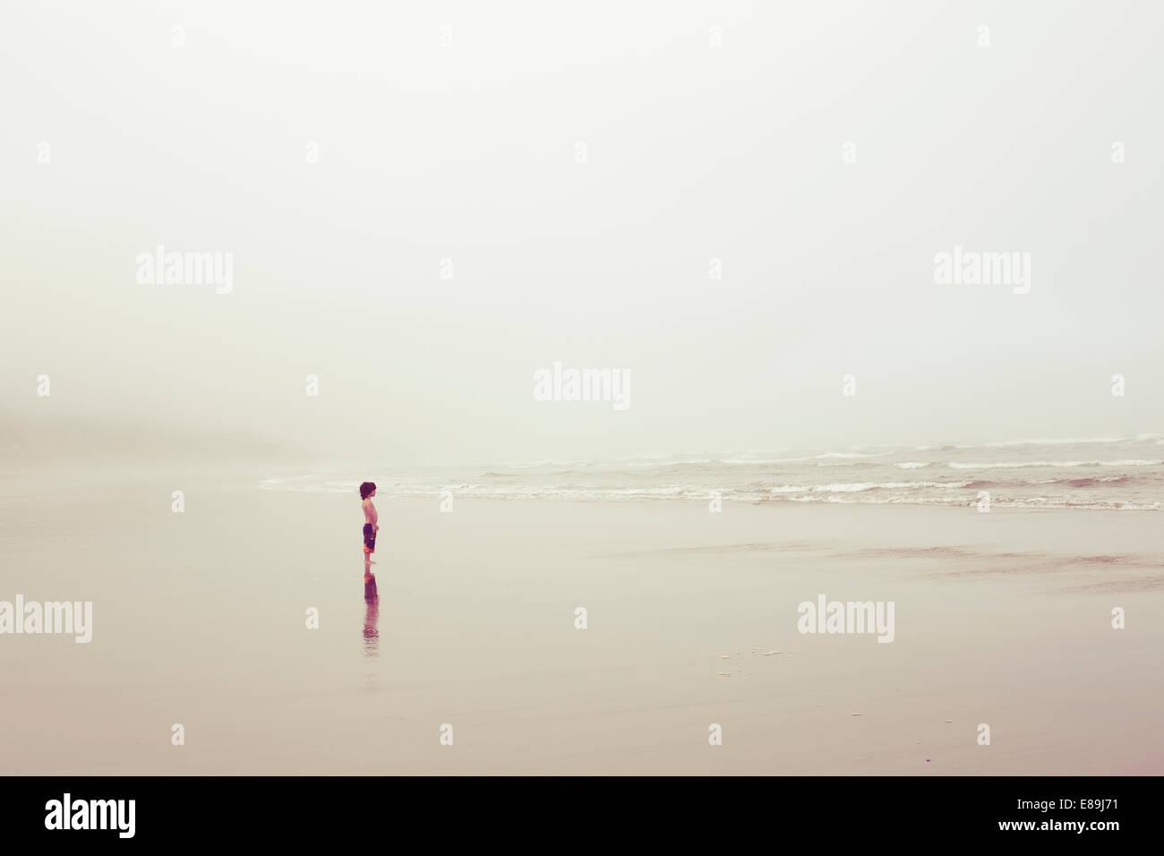 Junge am Meer an bewölkten Tag Stockbild