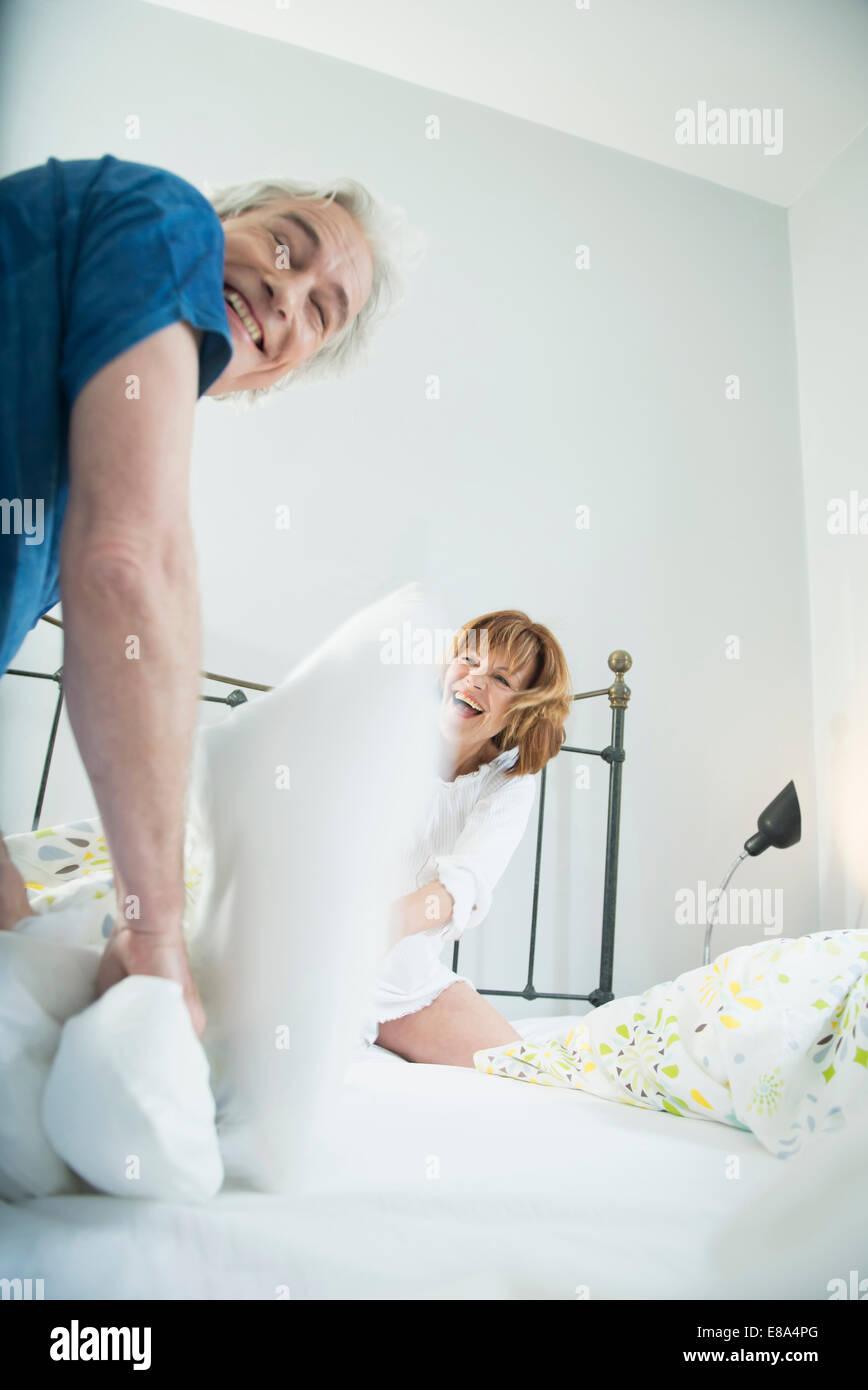 Paare, die Kissen zu kämpfen, im Bett, Lächeln Stockbild