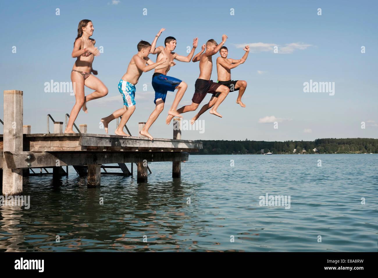 Fünf Jugendliche springen von einer Anlegestelle in See Stockbild