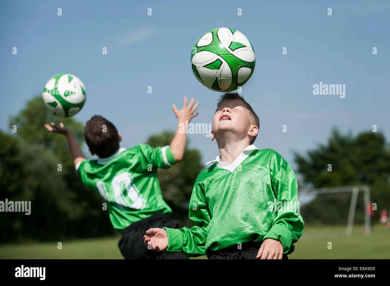 Zwei junge Fußballer lernen Kugel Steuern Stockbild