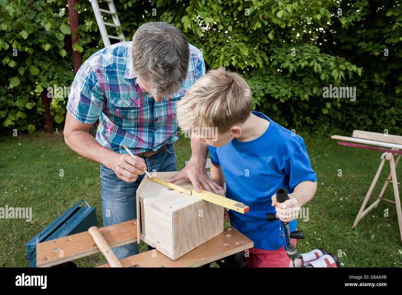Messung der Holz Vogelhaus bauen Vater Sohn Stockbild