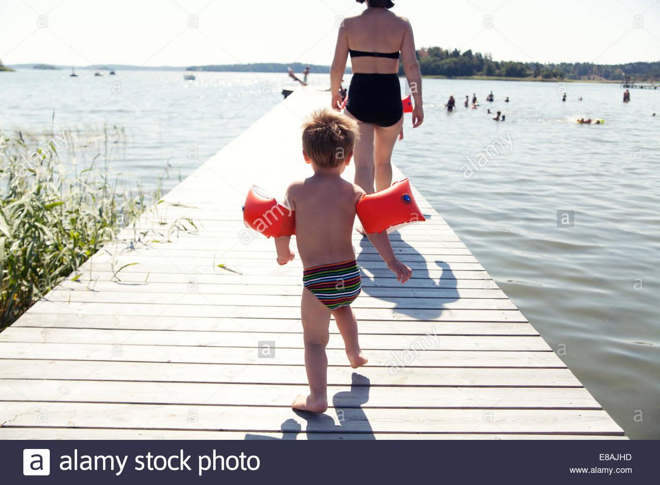 Rückansicht des männlichen Kleinkind nach Mutter entlang See pier Stockbild