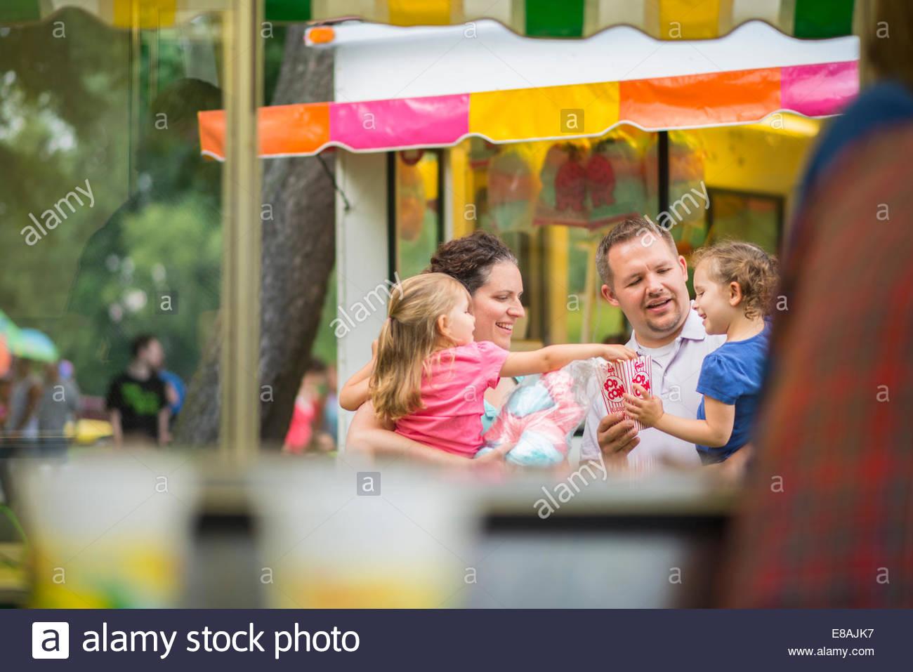 Mitte erwachsenes paar und zwei jungen Töchter Essen Popcorn Jahrmarkt Stockbild