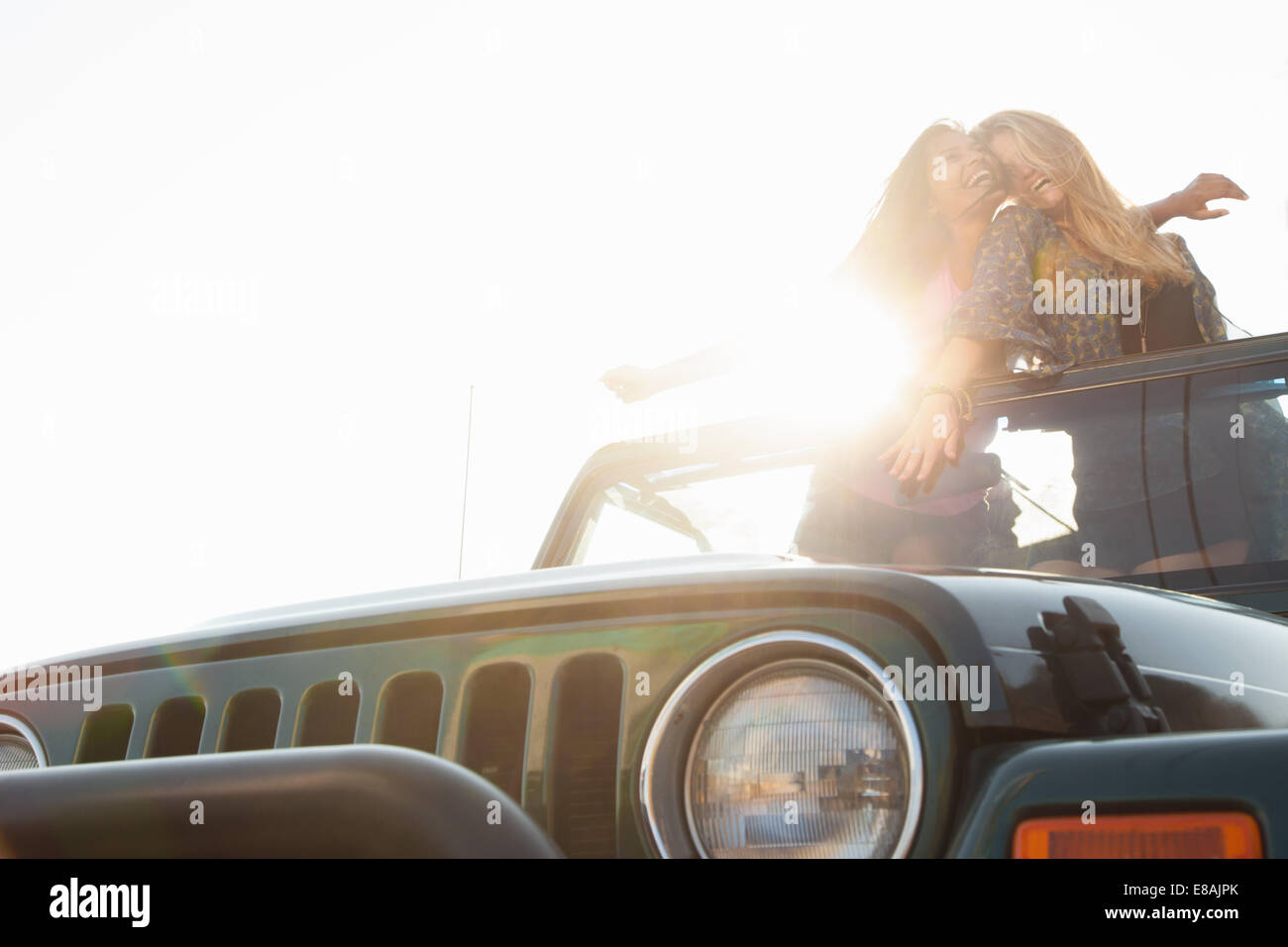Zwei junge Frauen stehen auf der Rückseite jeep Stockbild