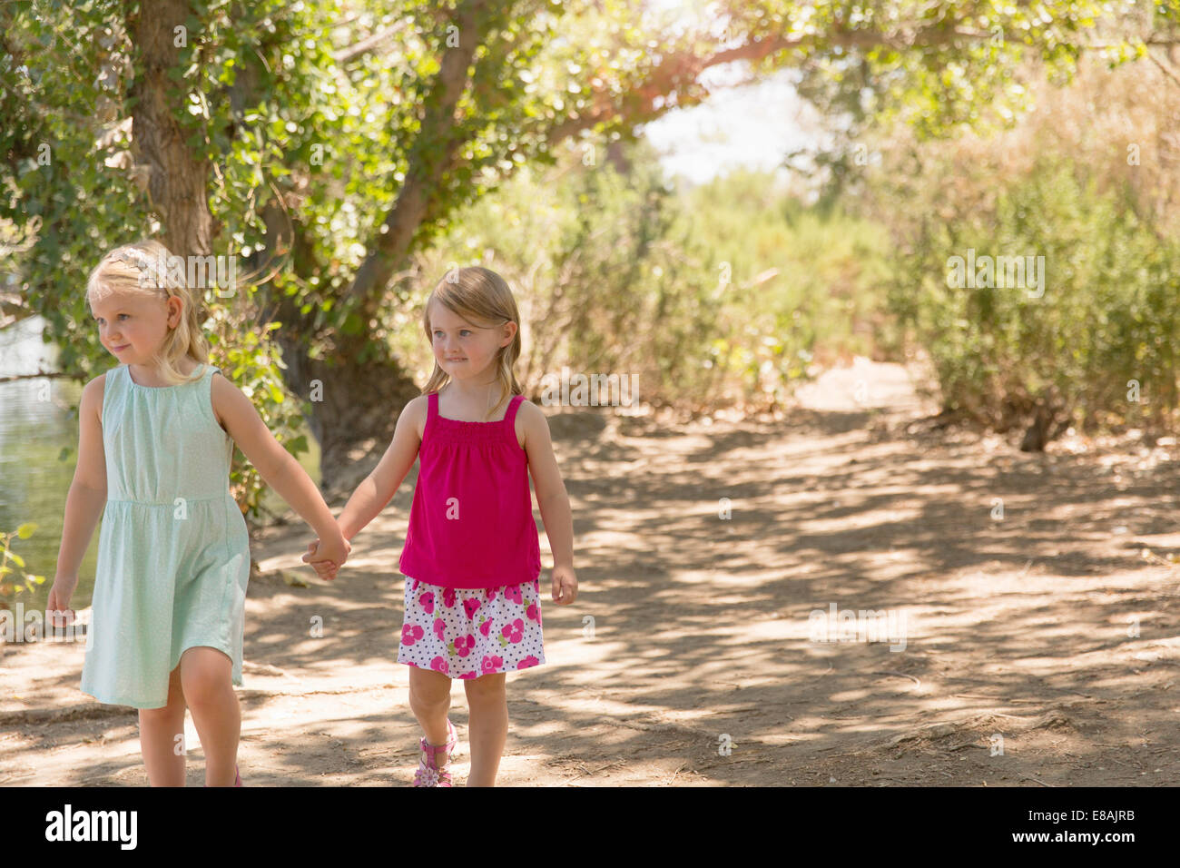 Zwei junge Schwestern flanieren und händchenhaltend am Ufer Stockbild