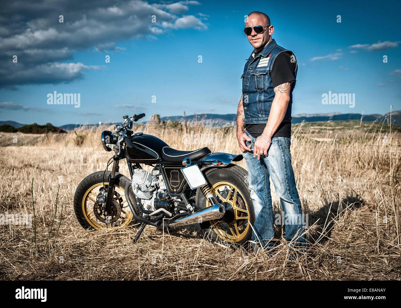 Porträt von männlichen Motorradfahrer in Ebene Landschaft, Cagliari, Sardinien, Italien Stockbild