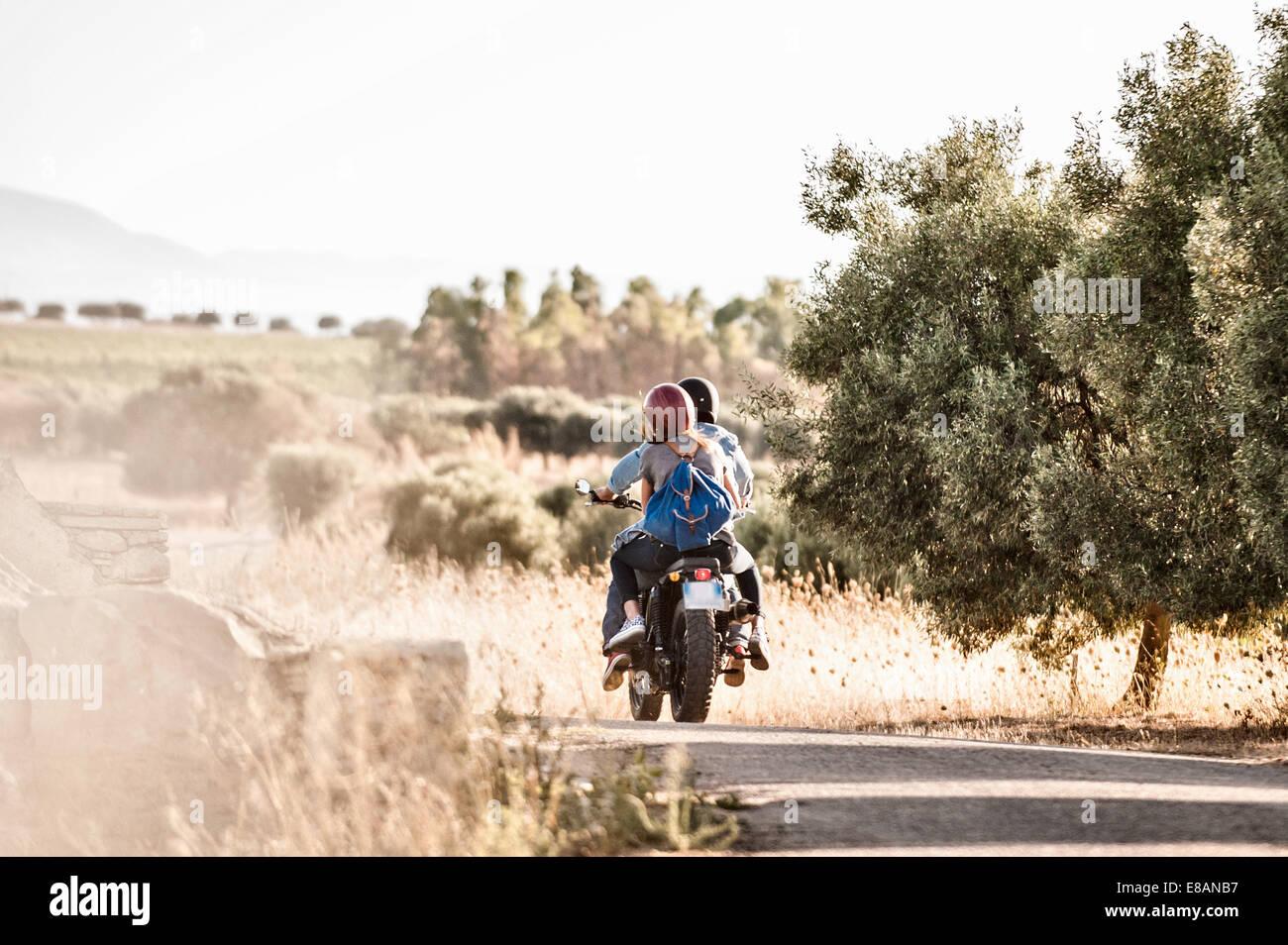 Rückansicht des Mitte erwachsenes paar Motorrad auf staubigen Feldweg, Cagliari, Sardinien, Italien Stockbild