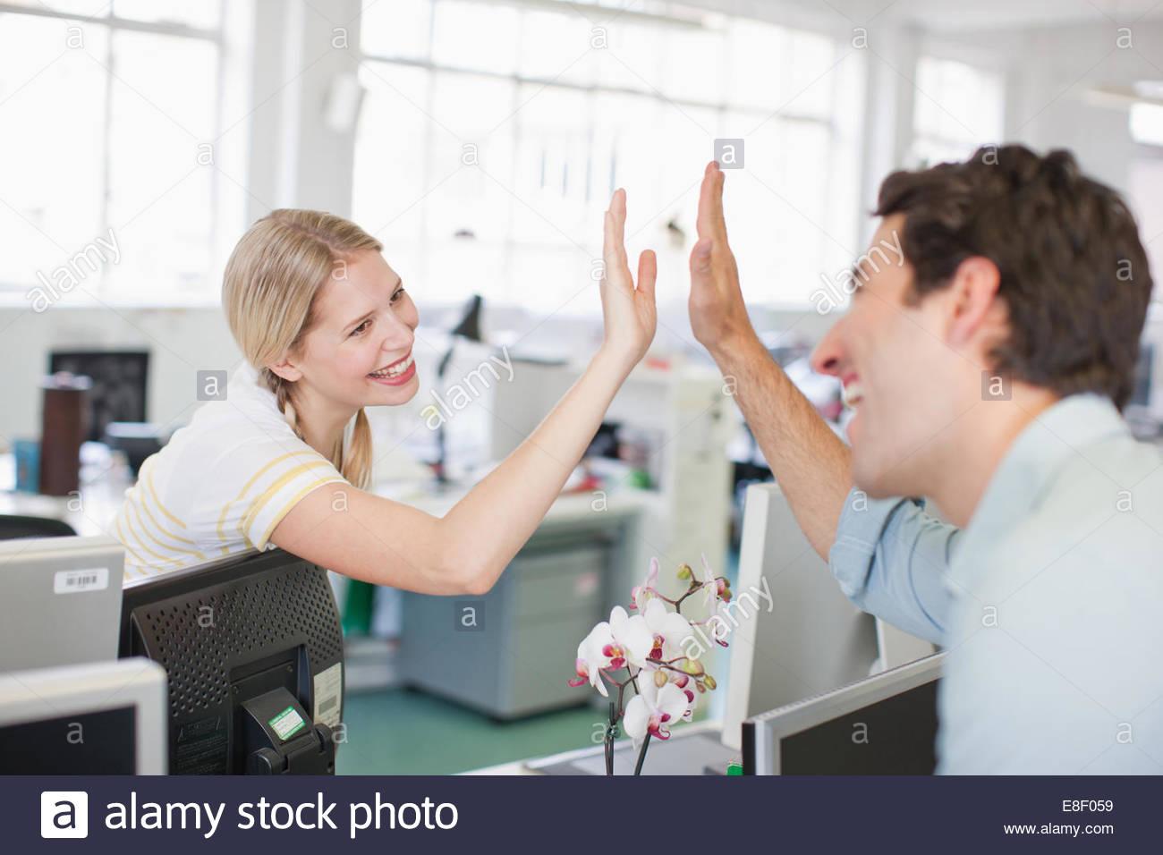 Business-Leute geben hohe fünf im Büro Stockbild