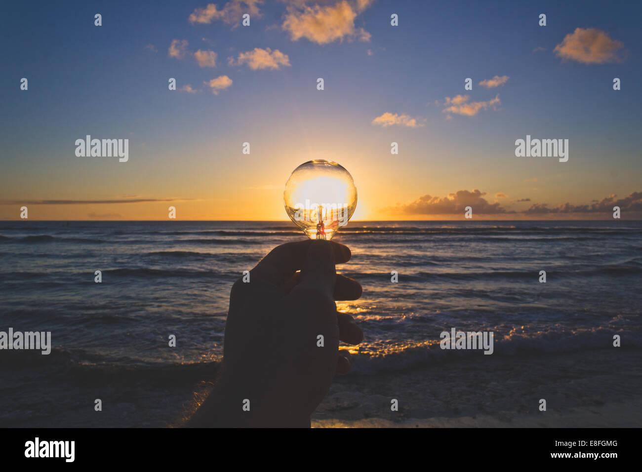 USA, Hawaii Inseln, Ansicht von Hand mit Glühbirne bei Sonnenuntergang Stockbild