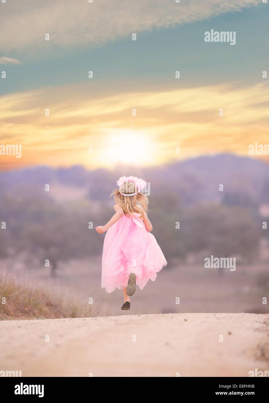 Mädchen tragen rosa Kleid, die Straße runter laufen Stockbild