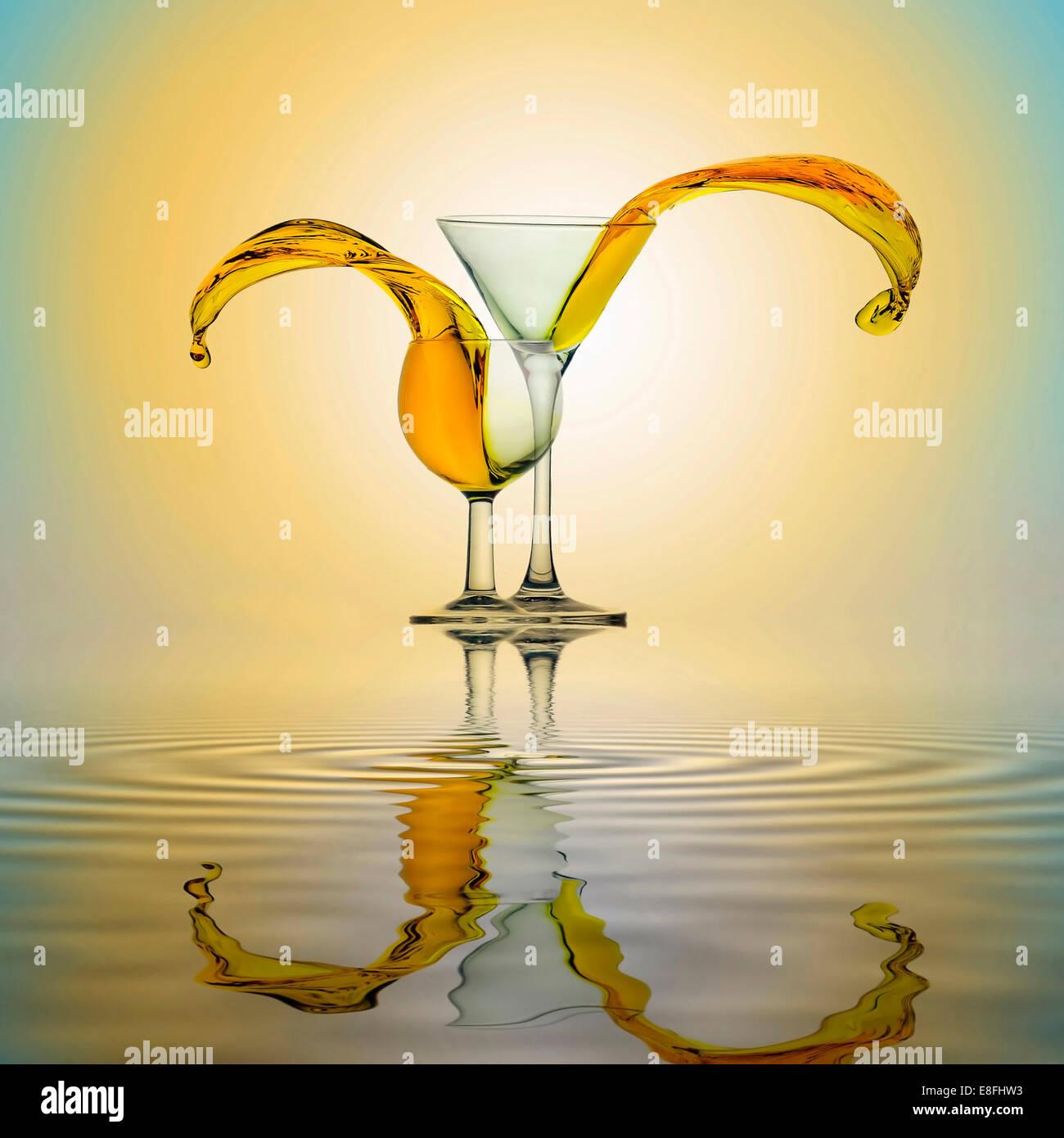 Gelbes Wasser spritzt aus zwei Gläsern, die nebeneinander stehen auf Wasseroberfläche Stockbild