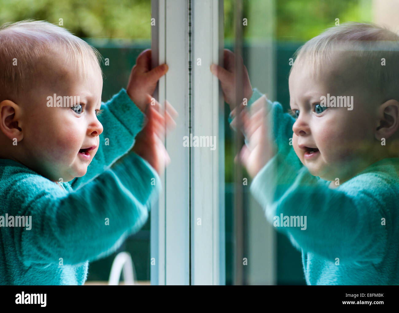 Baby Junge spielt mit seinem Spiegelbild im Fenster Stockbild