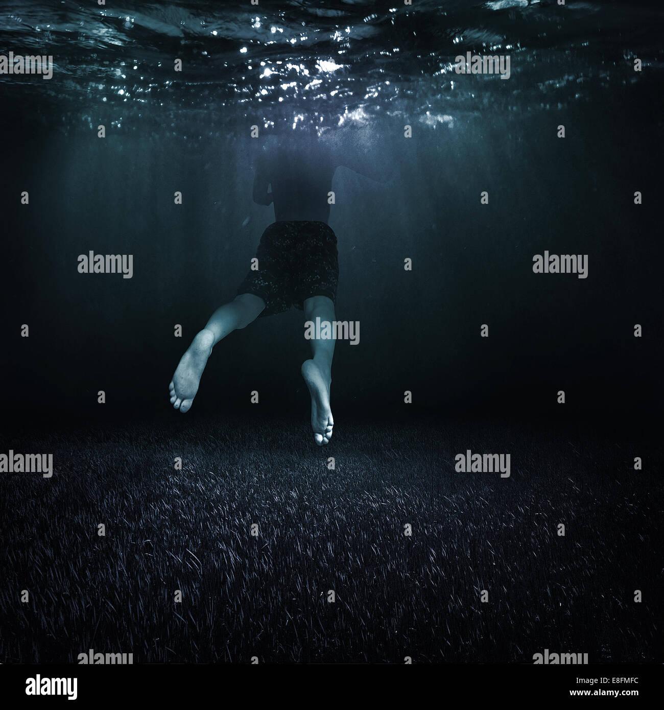 Kanada, British Columbia, Vancouver, Boy (10-11) Schwimmen im dunklen Wasser Stockbild