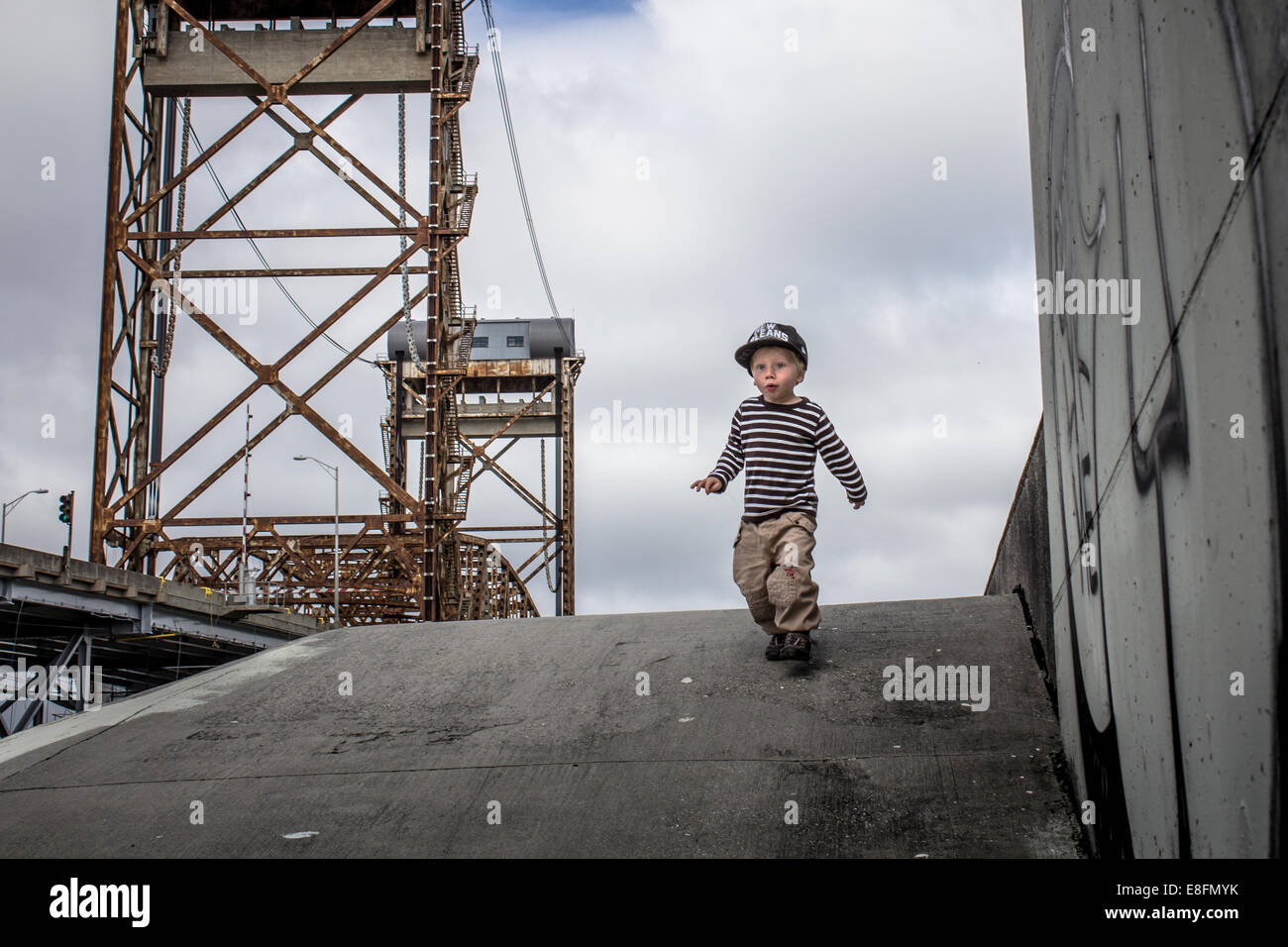 USA, Louisiana, New Orleans, Boy (2-3) vom Deich im unteren neunten Bezirk, Claiborne Bridge im Hintergrund läuft Stockbild