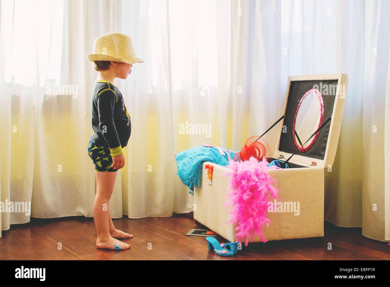 Junge (2-3) tragen großen Hut stehen durch verkleiden box Stockbild