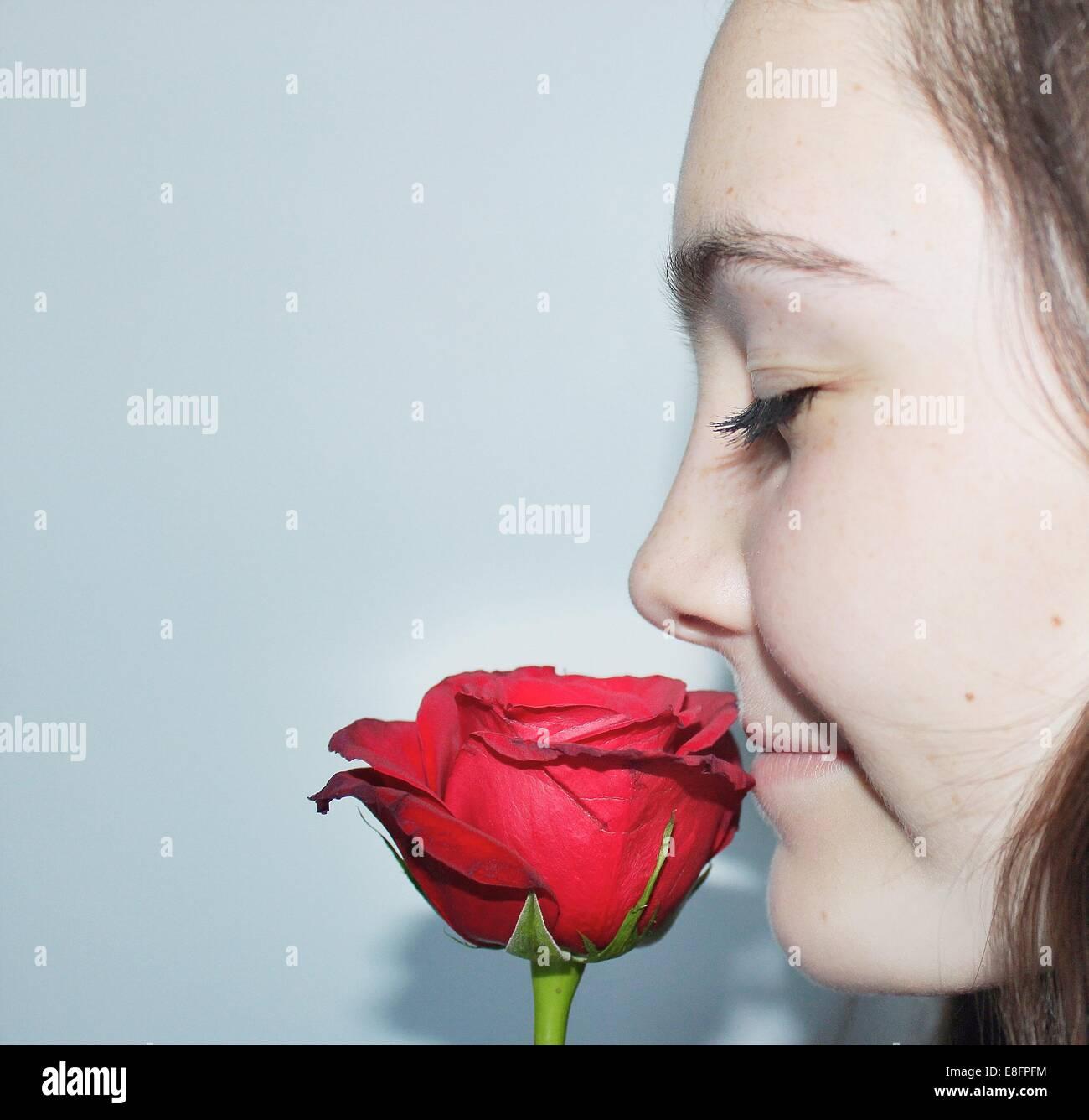Close-up Portrait eines Mädchens mit Augen geschlossen eine rose Blume riechen Stockbild