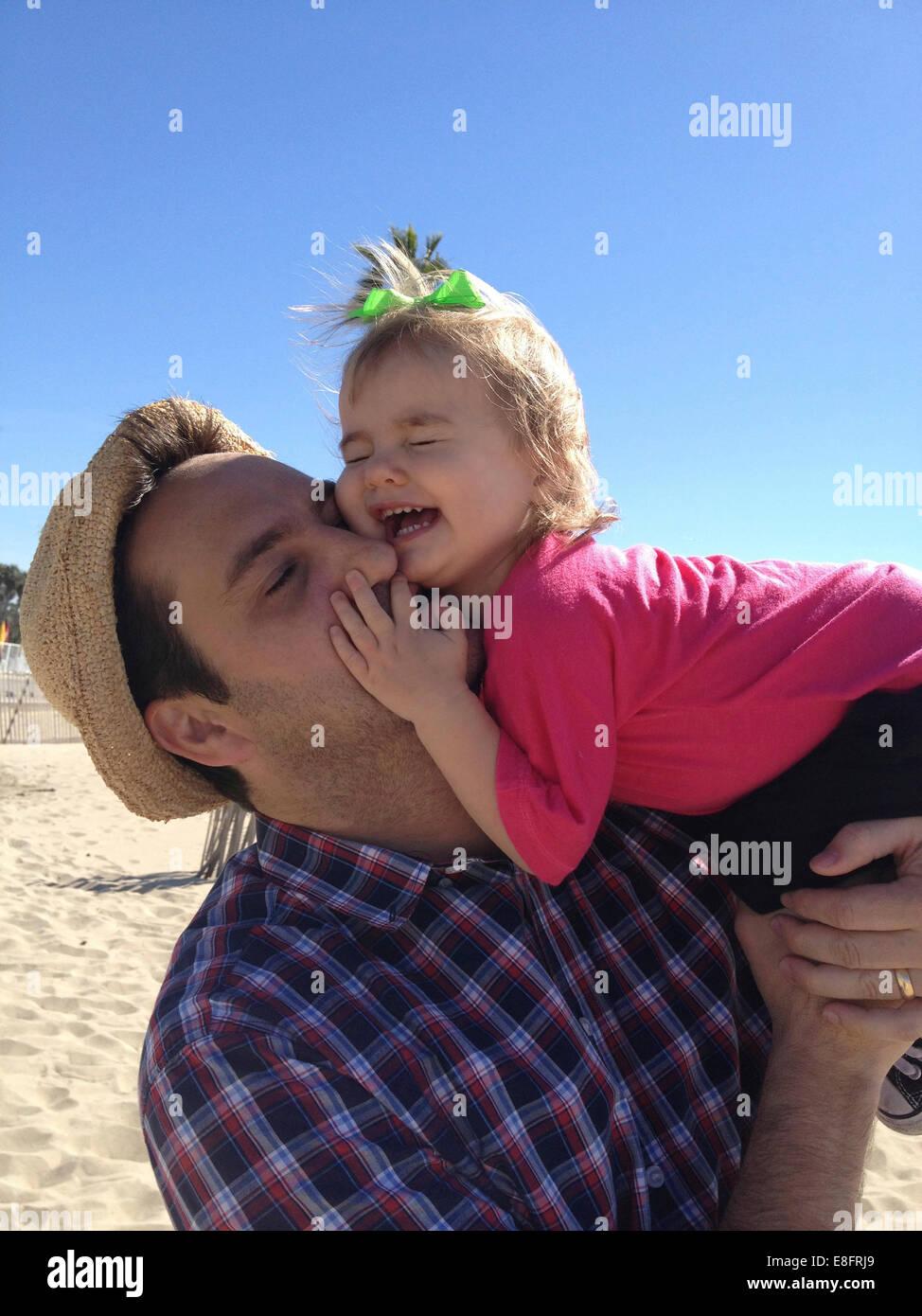 Vater und Tochter (18-23 Monate), die Spaß am Strand Stockbild