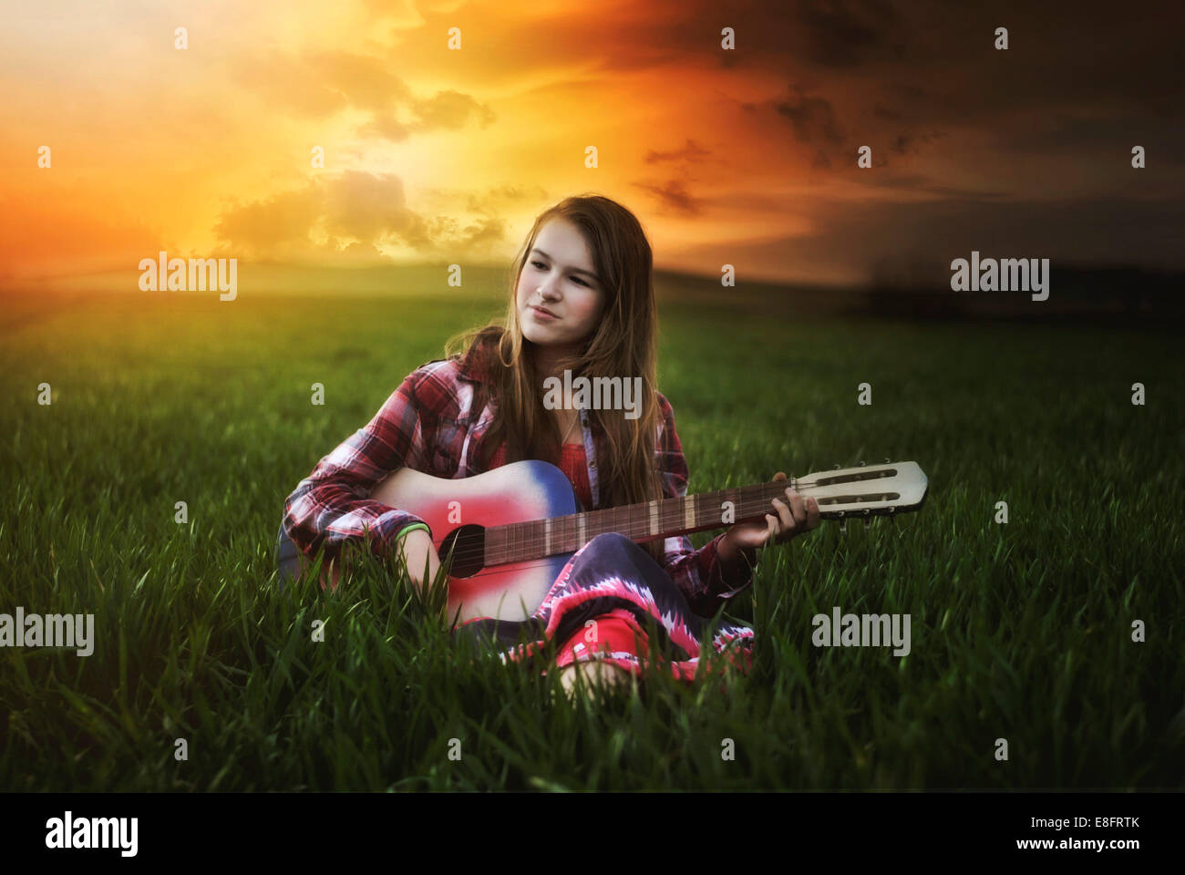 Mädchen sitzen im Feld bei Sonnenuntergang Gitarre spielen Stockbild
